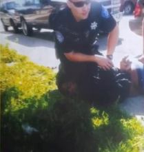 officer Brogden with his knee on Malad Baldwins neck during a act of police violence in 2014
